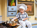 Little boy plays the cook sits on a kitchen table and Stock Photo