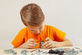 Little boy plays with metal constructor at table the Stock Photos