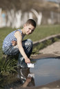 Little boy plays with paper boats in puddle happy Royalty Free Stock Photo