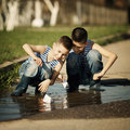 Little boy plays with paper boats in puddle two boys playing Stock Photo