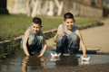 Little boy plays with paper boats in puddle two boys playing Royalty Free Stock Photos