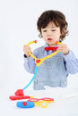 Little boy plays with toy phonendoscope and medical instruments on white background Royalty Free Stock Image