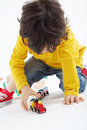 Little boy plays with toy train near wooden railway on white background Royalty Free Stock Photos