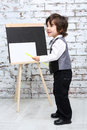 Little boy with pointer stands next to chalk board sheet in studio Stock Photos