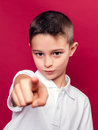 Little boy pointing at camera with his finger over a red background Stock Photo