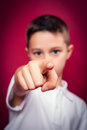 Little boy pointing at camera with his finger over a red background Royalty Free Stock Photos