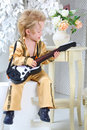 Little boy in pop retro suit playing the guitar portrait of a Stock Photos