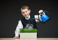 Little boy pouring home model and green grass portrait of with the help of water pot concept of investment real estate Royalty Free Stock Photo