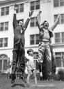 A little boy pretending to lift two grown men Royalty Free Stock Photo