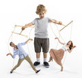 Boy puppeteer controlling parents with strings isolated on white Royalty Free Stock Photo