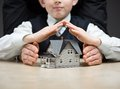 Little boy puts hands as roof over house model concept of real estate and protection Royalty Free Stock Photo