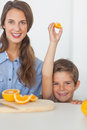 Little boy raising an orange segment in the kitchen with his mother Royalty Free Stock Photography