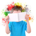 Little boy reading art book with paint on white a young is holding a blank colorful rainbow splatters coming out a background Stock Images