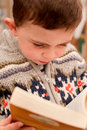 Little boy reading a book paperback novel in an outside library the focus of the image is on the child intently thereby Royalty Free Stock Photo