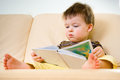 Little boy reading book on sofa Royalty Free Stock Photo