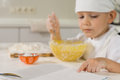 Little boy reading a recipe book as he bakes serious in an apron and white chefs toque in the kitchen Stock Images