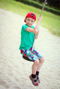 Little boy in red cap sit on swing rope outdoor activity Royalty Free Stock Image
