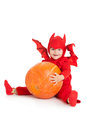Little boy in red devil costume sitting and holding big pumpkin over white background Royalty Free Stock Image