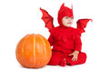 Little boy in red devil costume sitting near big pumpkin over white background Royalty Free Stock Image