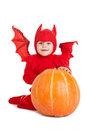 Little boy in red devil costume sitting near big pumpkin over white background Stock Image