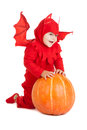 Little boy in red devil costume sitting near big pumpkin over white background Stock Photography