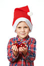 Little boy in red santa hat with shiny christmas balls and his hand Stock Photos
