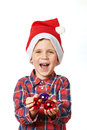 Little boy in red santa hat with shiny christmas balls and his hand Royalty Free Stock Images