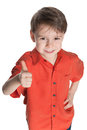 Little boy in the red shirt holds his thumb up on white background Royalty Free Stock Photography