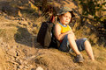 Little boy relaxing during a hiking expedition cute sitting down on the ground in summer Stock Image