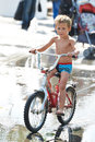 Little boy rides his bike among puddles in summer day Royalty Free Stock Photo