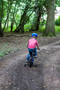 Little boy riding bike through woods Stock Photo