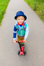 Little boy riding scooter to school, high angle Royalty Free Stock Photo