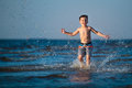 Little boy running through the water at beach Stock Photos