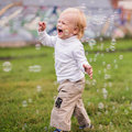 Little boy runs and catches soap bubbles outdoors Stock Photo