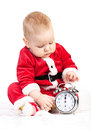 Little boy in santa costume with alarm clock cute playing on white background Royalty Free Stock Image