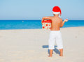 Little boy in santa hat back view of cute with gift on tropical vacation Royalty Free Stock Photos