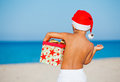Little boy in santa hat back view of cute with gift on tropical vacation Stock Photos