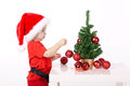 Little boy with santa hat cute decorates christmas tree Royalty Free Stock Images