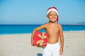Little boy in santa hat cute with gift on tropical vacation Stock Photos
