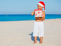 Little boy in santa hat cute with gift on tropical vacation Stock Images