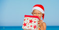 Little boy in santa hat cute with gift on tropical vacation Royalty Free Stock Photo