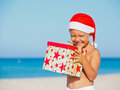Little boy in santa hat cute with gift on tropical vacation Royalty Free Stock Images