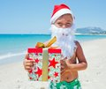 Little boy in santa hat cute with gift on tropical vacation Stock Photography