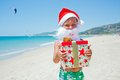 Little boy in santa hat cute with gift on tropical vacation Royalty Free Stock Image