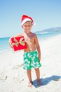 Little boy in santa hat cute with gift on tropical vacation Stock Image