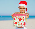 Little boy in santa hat cute with gift on tropical vacation focus on the gift Royalty Free Stock Image