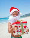 Little boy in santa hat portrait of cute with gift on tropical vacation Stock Image