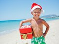 Little boy in santa hat portrait of cute with gift on tropical vacation Royalty Free Stock Images