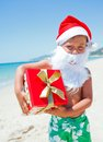 Little boy in santa hat portrait of cute with gift on tropical vacation Royalty Free Stock Photos