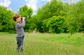 Little boy scanning the woods with binoculars Royalty Free Stock Photo